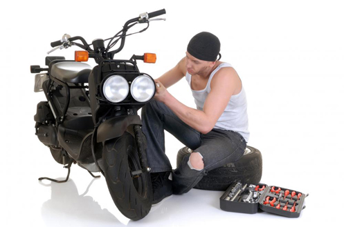 Man working on motorcycle. Image Source: http://images.wisegeek.com/man-working-on-motorcycle.jpg